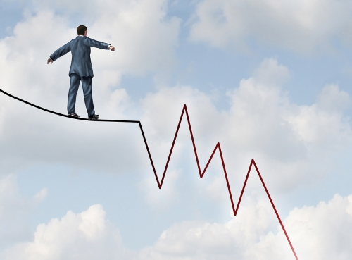 Losing Profit risk and Investment danger as a financial and business concept or metaphor facing wealth adversity as a businessman walking on a high wire tight rope shaped as a negative and downward stock market sell graph.